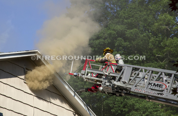 firefighter on aerial ladder tip at house fire