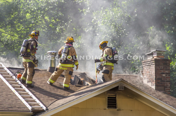 firefighters on roof after cutting a vent