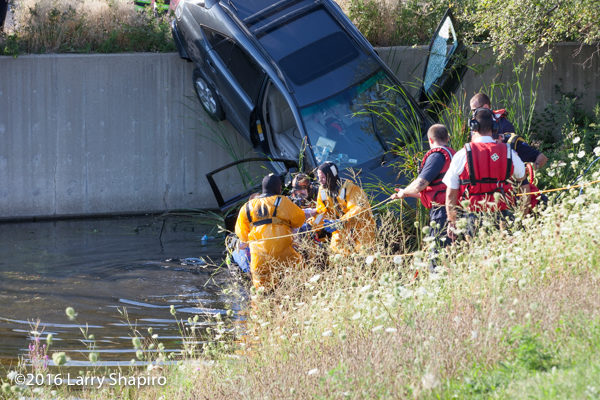 fire department divers rescue the driver from a car on a retaining wall