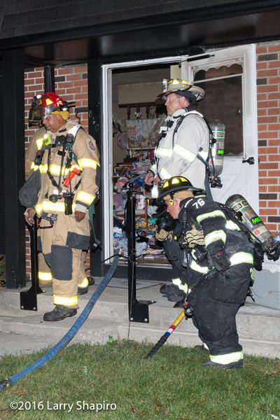 firefighters at door of townhouse fire