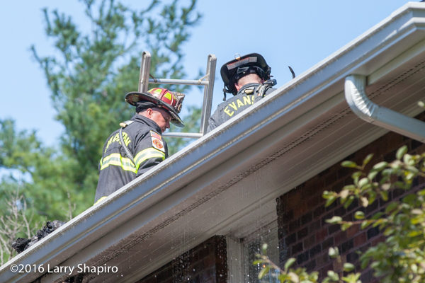 firefighters on roof of house fire