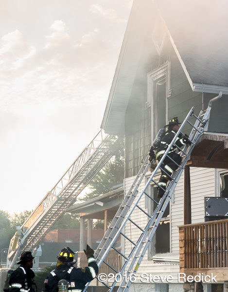 firefighters carry ladders at house fire