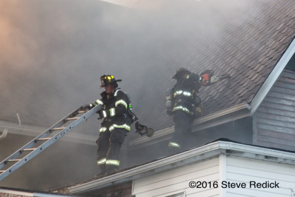 firefighters on house fire roof with smoke