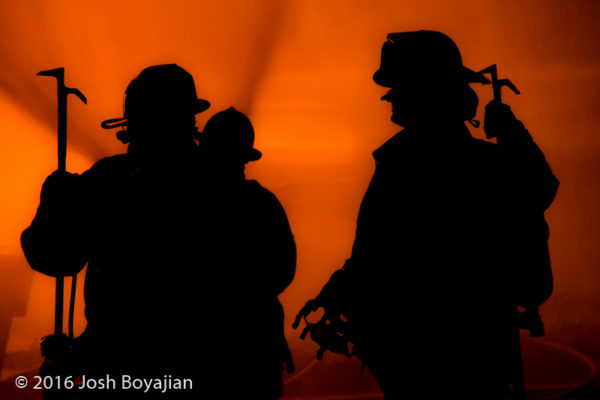 silhouette of firefighters by house fire