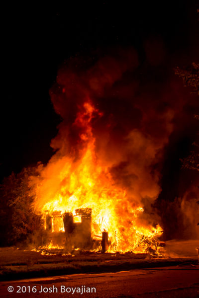 vacant house fully engulfed in flames at night
