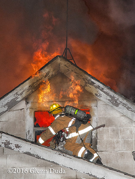 firefighter on roof with heavy fire
