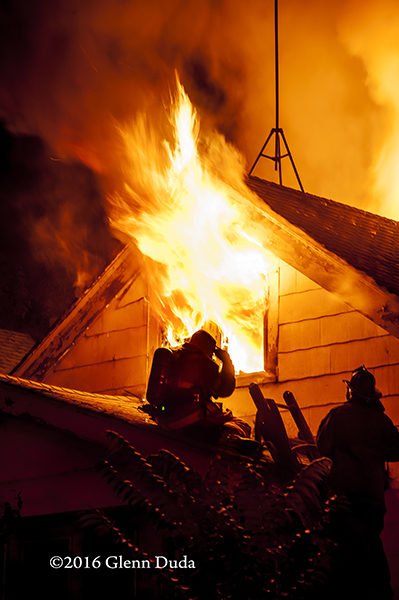 silhouette of firefighters on roof