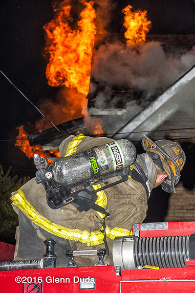 Detroit firefighter on engine at night