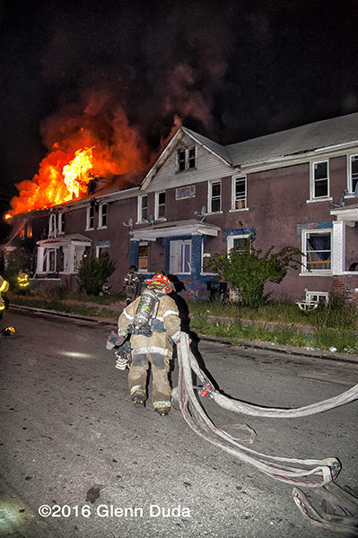 firefighter lays out hose at night fire scene