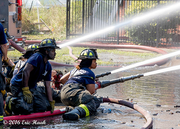 African American firefighters with hose line