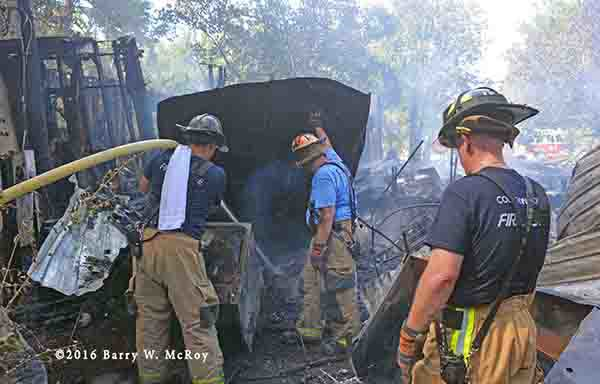 firefighters overhaul rural fire scene