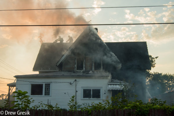 firefighters on the roof during a house fire