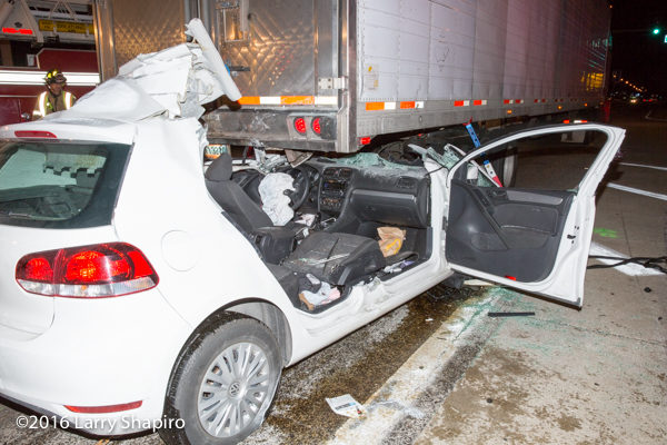 car wedged under semi trailer