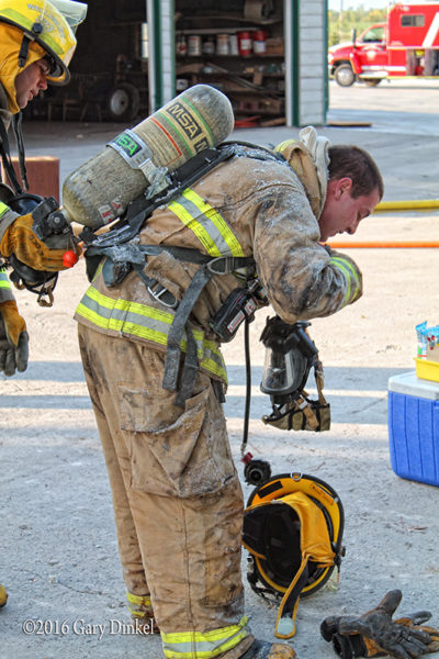 firefighter removes mask after a fire
