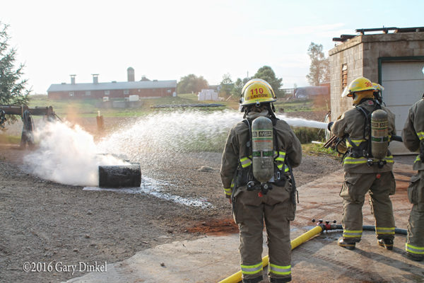 firefighter with hose douses smoldering fire