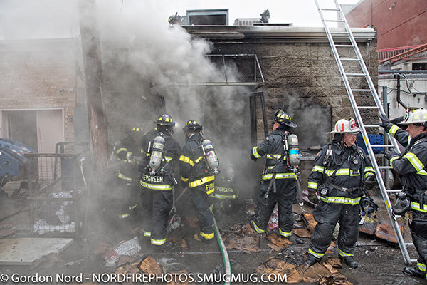 firefighters at fire scene with hose line