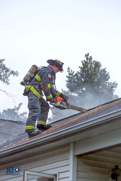 firefighter ventilates roof during fire
