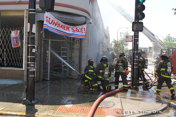 firefighters with hose line at building fire