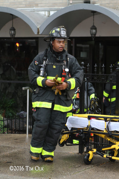 firefighter in PPE with tools after a fire