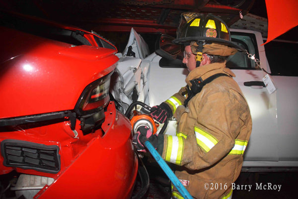 firefighter uses Holmatro tools to cut driver from car
