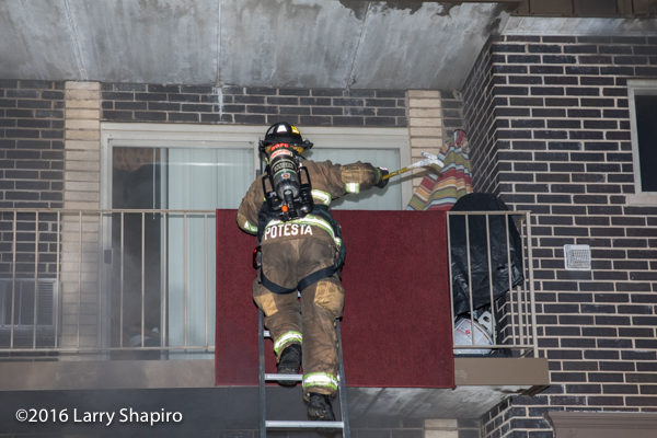 firefighter climbs ladder to balcony