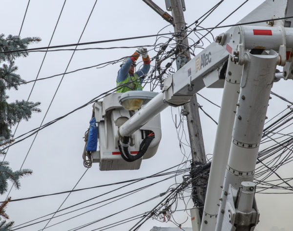 utility worker in bucket with power lines