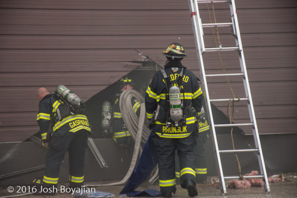 firefighters cut through overhead door