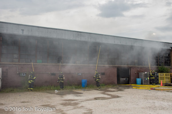firemen break windows at warehouse with pike poles