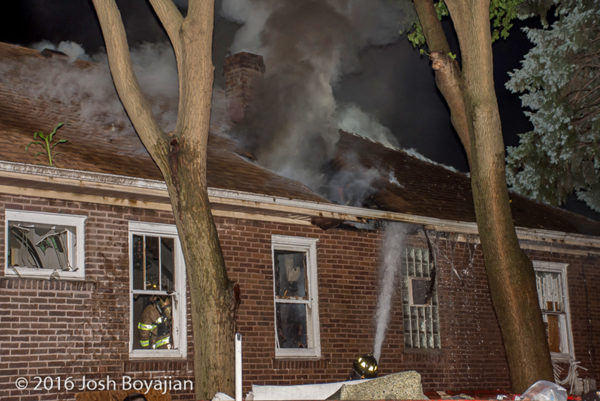 heavy smoke through roof of a house on fire
