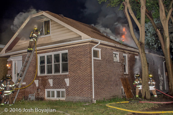 firefighters battle fire through the roof of a house on fire