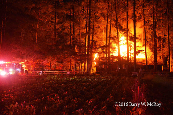 mobile home engulfed in flames at night in rural area