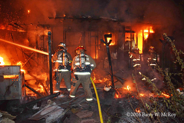 firefighters battle mobile home fire at night