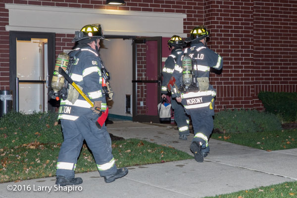 Firefighters enter building with tools and PPE