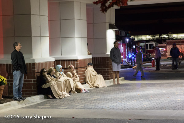 hotel guests wrapped in blankets outside hotel