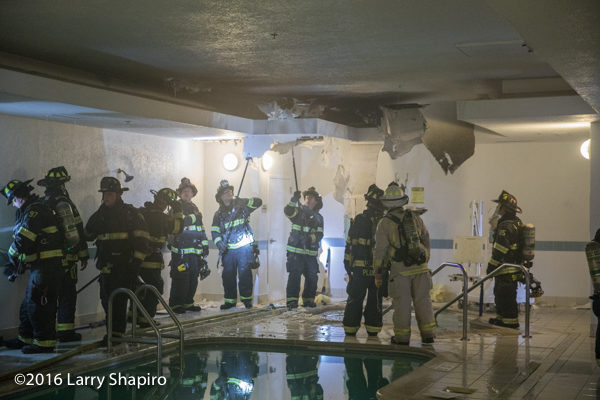 firefighters overhaul after fire near indoor pool
