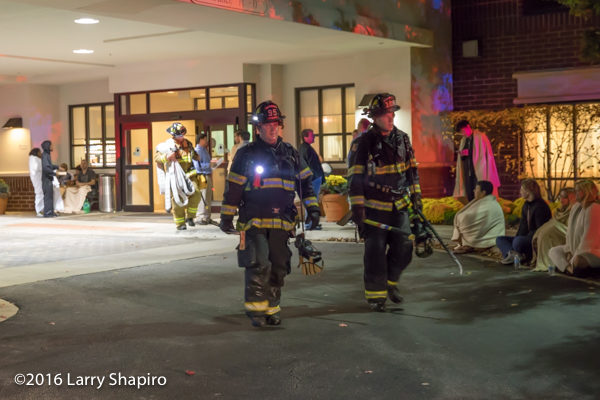 Firefighters in PPE with tools leave hotel after fire