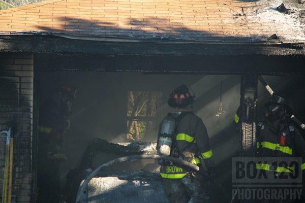 firefighters wash down the aftermath of attached garage fire
