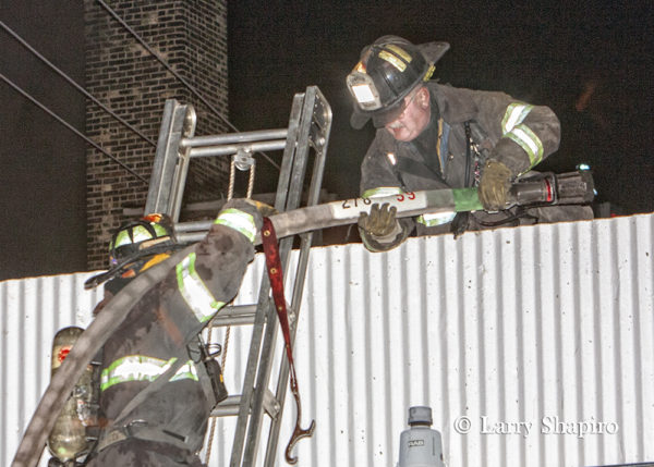 Firefighters manage hose line on ground ladder