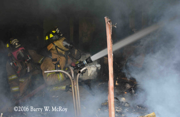 firefighter with hose line inside fire building