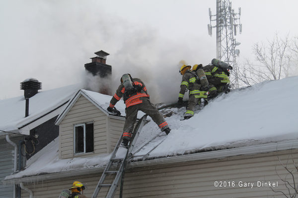 firefighters on house fire roof covered in snow