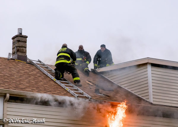 flames through the roof of a house with Firefighters