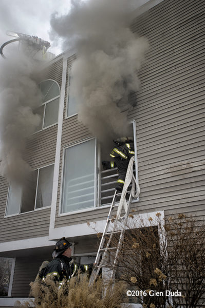 firefighter enters window from ladder with smoke