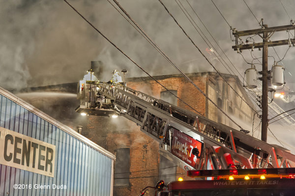 Firefighters in tower ladder bucket battle warehouse fire