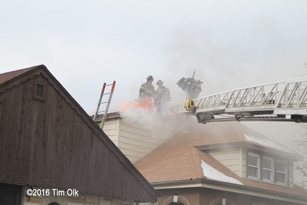 Firefighters venting roof with flames and smoke