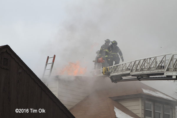 Firefighters after venting roof with flames and smoke