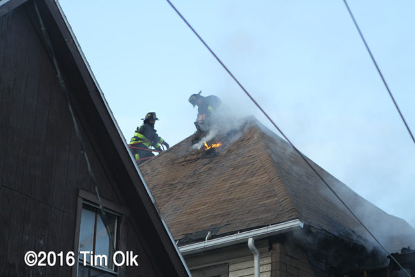 Firefighters venting a house roof