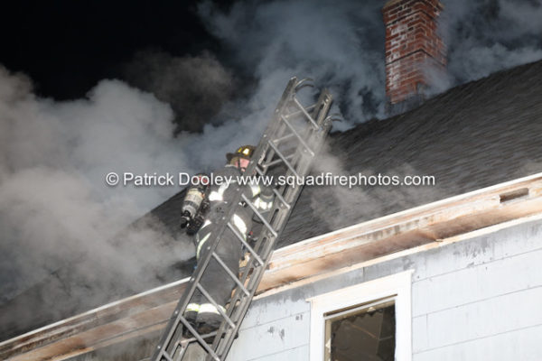 firefighter on ladder carrying a roof ladder