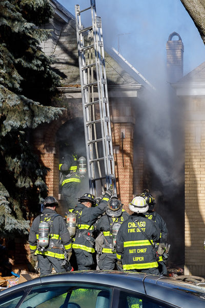 firefighters position ground ladder during fire