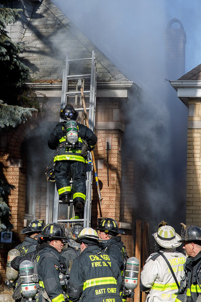 firefighter climbs ground ladder during fire