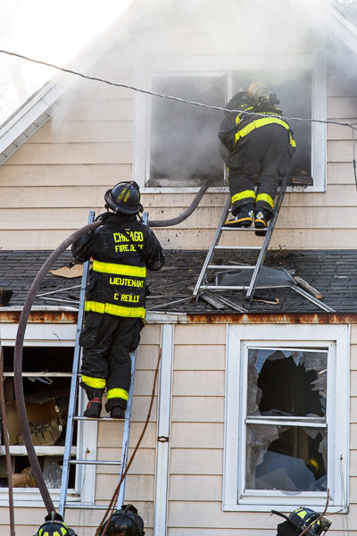 firefighters work from ground ladders at fire